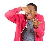 man pinching his nose as something stinks